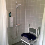 Blue floored wet room with toilet, a shower and a shower seat.